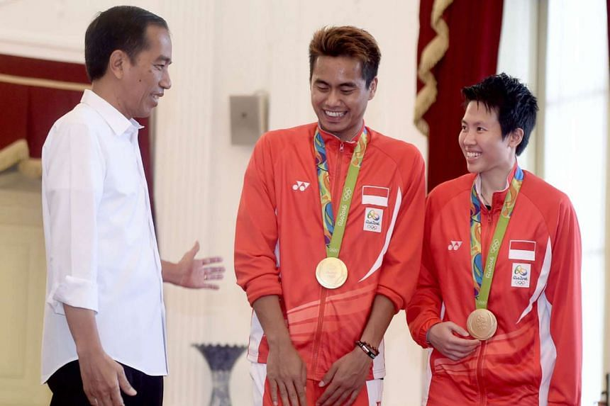 Above: Indonesian President Joko Widodo (left) congratulates gold medallists Liliyana and Tontowi at his office in Jakarta.