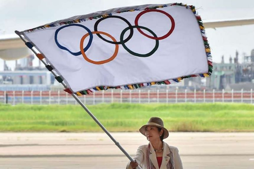 Tokyo Governor Yuriko Koike displays the Olympic flag at an arrival ceremony at Tokyo's Haneda airport yesterday, after disembarking with the flag from an All Nippon Airways plane.