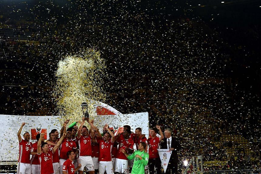 Bayern Munich players celebrate with the trophy after winning the German Super Cup on Aug 14, 2016.