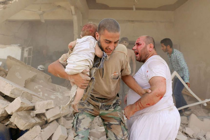 A Syrian man carries a wounded child following the barrel bomb attack.