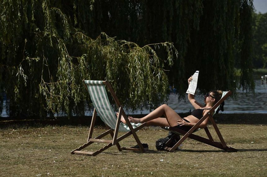 A woman relaxes on a deckchair on a sunny afternoon in Regents Park in London, Britain, August 24.