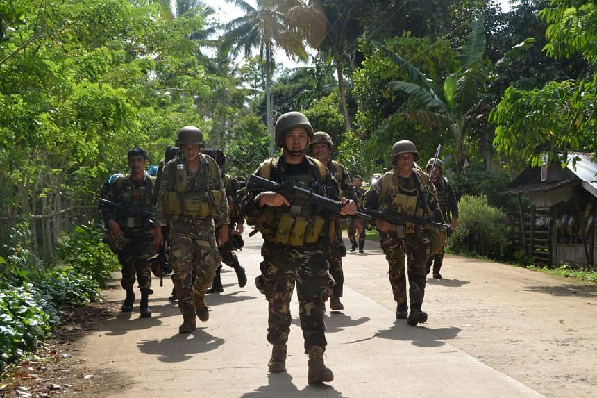 Philippine soldiers return to camp after an armed encouter with members of militant group Abu Sayyaf at the village of Bongkaong, Patikul town, Sulu province on Aug 26, 2016.