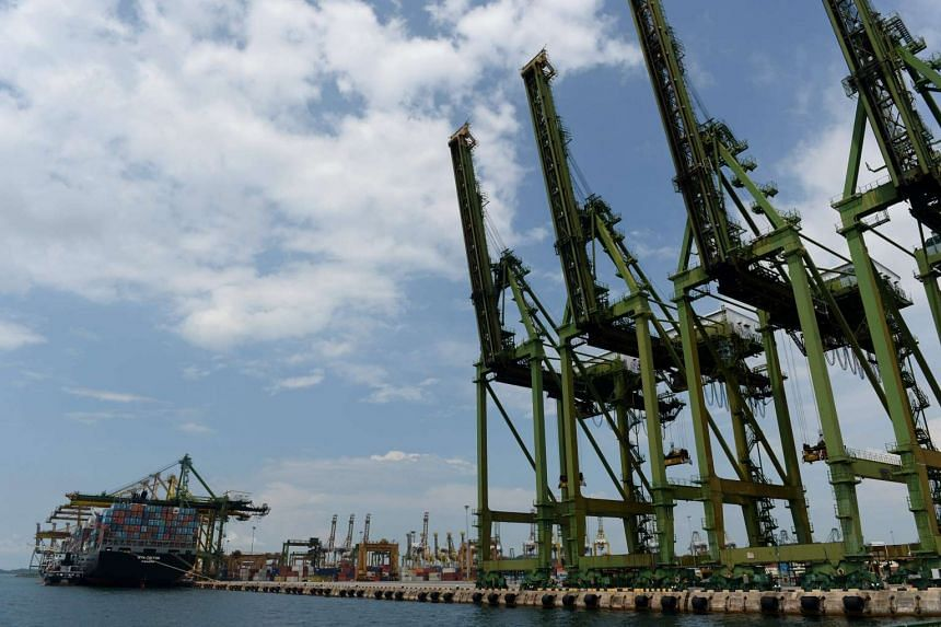 A vessel docking at the port in Singapore on Aug 17. Manufacturing output last month shrank 3.6 per cent year on year.
