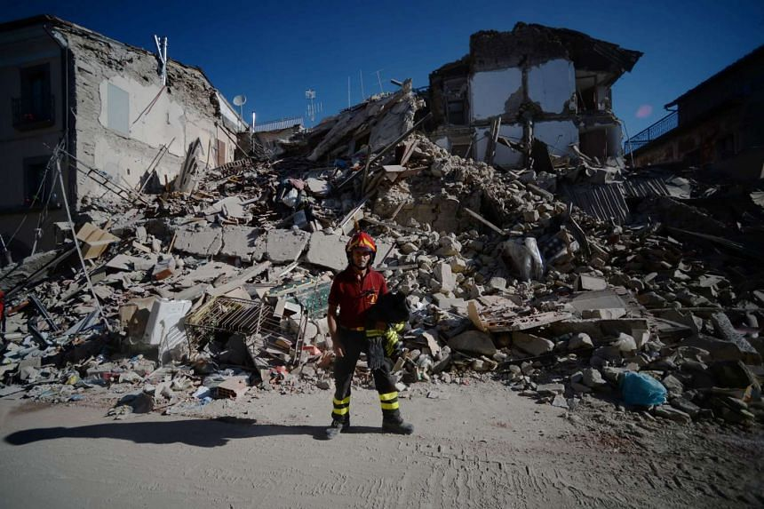 A fireman stands next to ruins in the central destroyed street of Amatrice in central Italy on August 25, after a strong eartquake that claimed at least 247 lives in Central Italy.