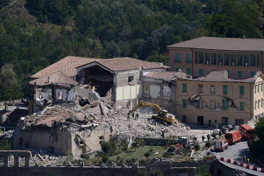 Rescue and emergency service personnel use an excavator to search for victims under the remains of a building at the damaged central Italian village of Amatrice, on Aug 25, 2016, a day after a 6.2-magnitude earthquake struck the region killing some 2