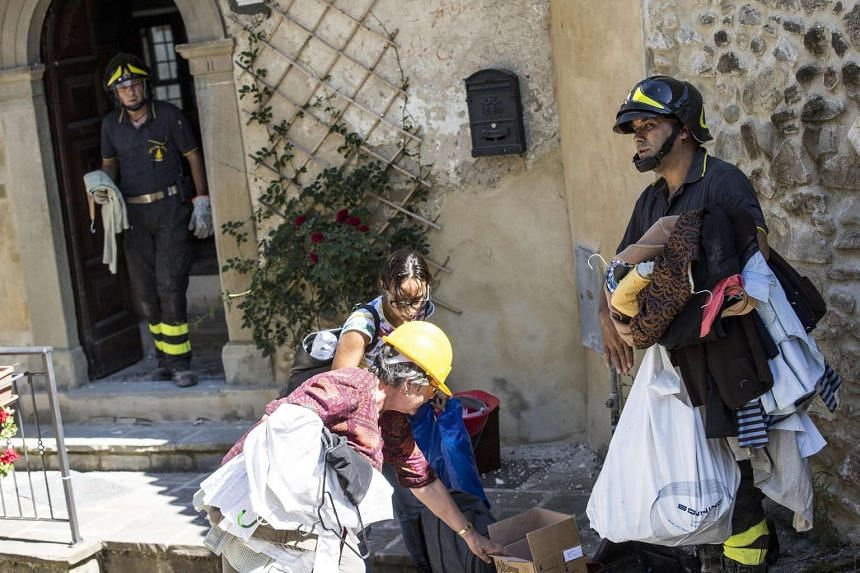Firemen help in recovery work in Accumoli, Italy, August 25, after the 6.2 earthquake struck Italy the day earlier that killed at least 247 people.