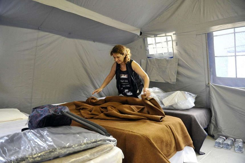 Woman arranges the bed in her room in a tent camp in Arquata Del Tronto, Italy, August 25, after the 6.2 earthquake struck Italy the day earlier that killed at least 247 people.