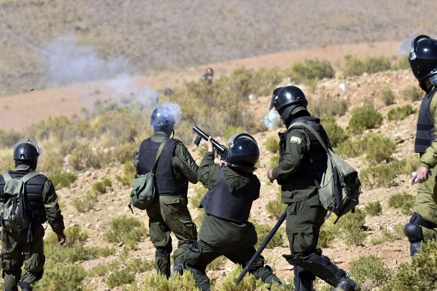 Riot policemen shoot tear gas during clashes with miners in Panduro, La Paz department, Bolivia on Aug 25, 2016.