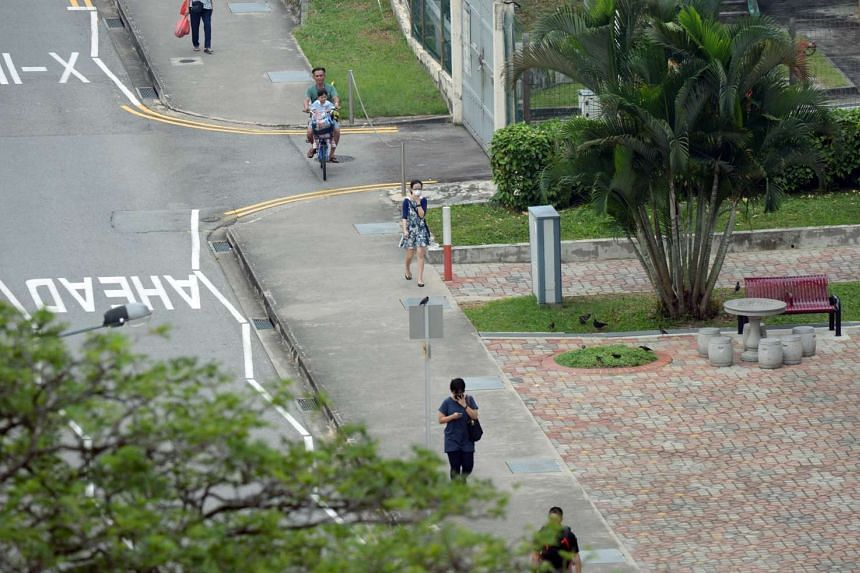 A woman wearing a mask and another covering her nose and mouth walking along Toa Payoh North.