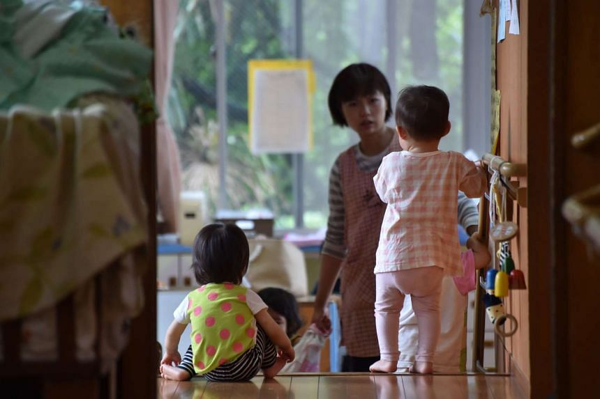 This picture taken on June 29, 2016 shows an employee of an official nursery school taking care of young children in Yokohama. Japanese Prime Minister Shinzo Abe has come under fire for his call for the nation's women to both bear more children to st