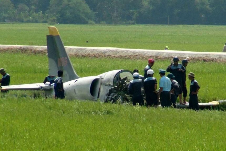 Soldiers and rescuers stand next to the crashed military aircraft on a rice field in the outskirts of Tuy Hoa in the central province of Phu Yen on Aug 26, 2016.