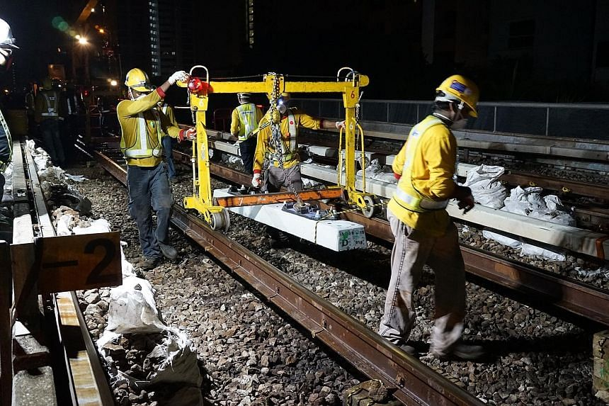 Workers replacing timber sleepers with longer-lasting concrete ones on the East-West Line. The entire project will be completed by the end of this year. The deadline had earlier been pushed back to early next year following a massive breakdown in Jul