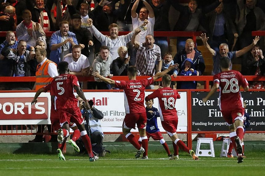 Accrington players celebrating their giant-killing feat after Matty Pearson's (No. 2) winner late in extra time gave the League Two side a 1-0 win over their Premier League opponents Burnley.