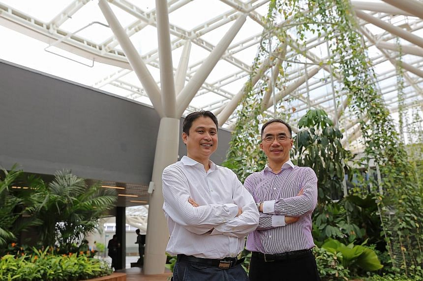 Dr Goh Chin Foo (far left) and Adjunct Associate Professor Matthew Tan at the atrium in NTU. The coating was applied to the atrium's roof, and has helped to reduce the temperature by some 8 deg C.