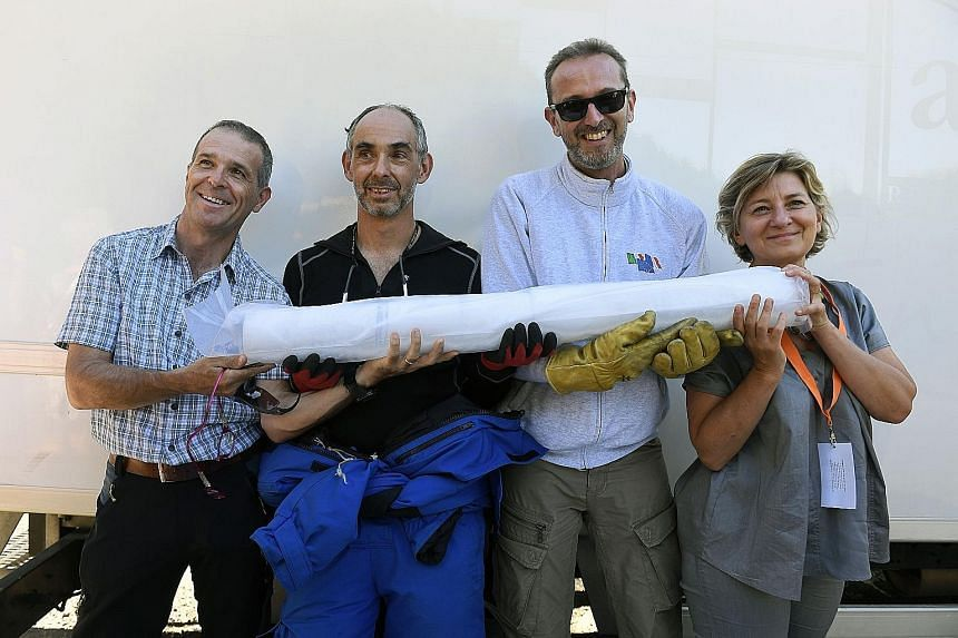 Researchers (from left) Carlo Barbante, Patrick Ginot, Jerome Chappellaz and Anne-Catherine Ohlmannpose with an ice core sample in Chamonix, eastern France, after extracting two of them - each over 120m long - from a Mont Blanc glacier. The two ice c