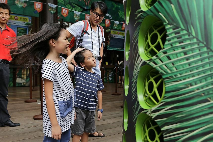 Steffi Teo, eight, and her brother, Leroy, six, enjoying the breeze from the Airbitat Smart Cooler. With them is their father, Mr Steven Teo, 38. If the trial at the zoo's ticketing area is successful, cool zones will be set up at all four wildlife p