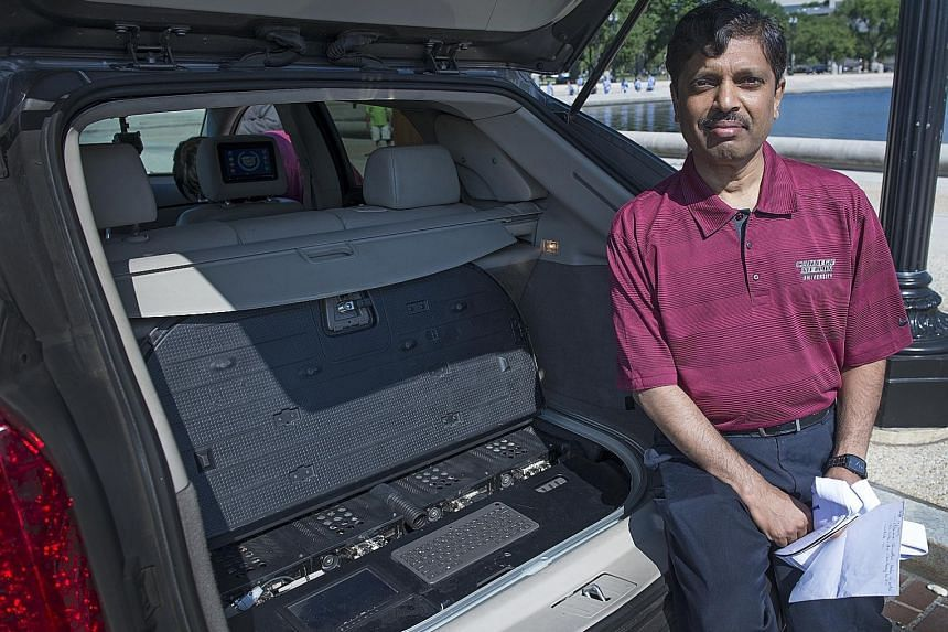 Carnegie Mellon University don Raj Rajkumar, shown here in 2014 with the main control centre of a self-driven car. He is more convinced than ever that introducing safe-driving features - lane-departure warnings, cameras and sensors - gradually is the