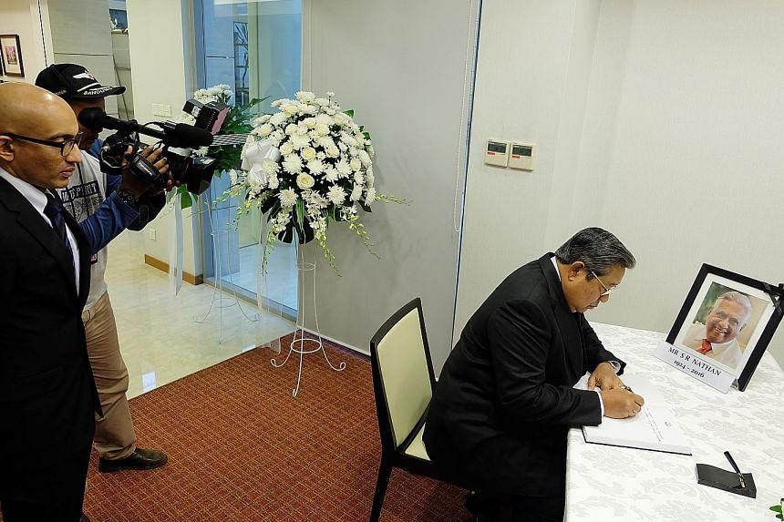 Dr Yudhoyono signing the condolence book for Mr Nathan at the Singapore Embassy in Jakarta yesterday as Singapore's Ambassador to Indonesia Anil Kumar Nayar looked on.