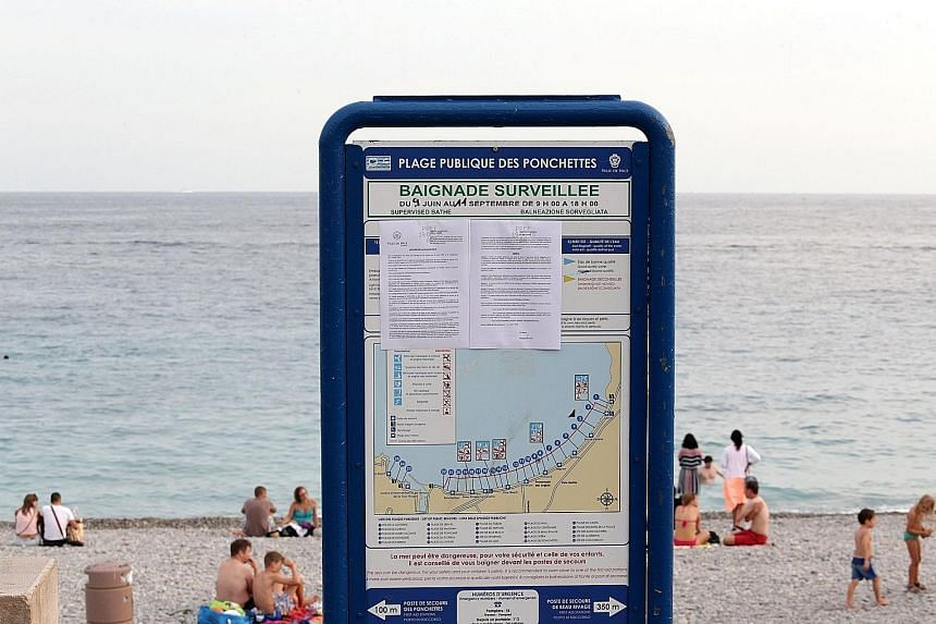 This file photo taken on Aug 19 shows the bylaw forbidding women to wear the burkini at the Ponchettes beach in Nice, south-eastern France. Around 30 French towns have banned the burkini, an Islamic swimsuit which covers the hair, but leaves the face