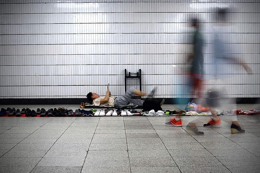 A shoe vendor waiting for customers in a Beijing underpass. The P2P lending sector has been a source of funds for individuals and small businesses overlooked by China's traditional financial services institutions, which prefer big borrowers with bett