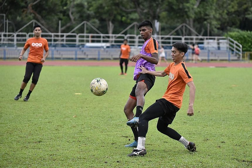 Hougang United striker Iqbal Hussain (in purple vest) challenges Haidil Sufian for the ball during training at Hougang Stadium on Wednesday.