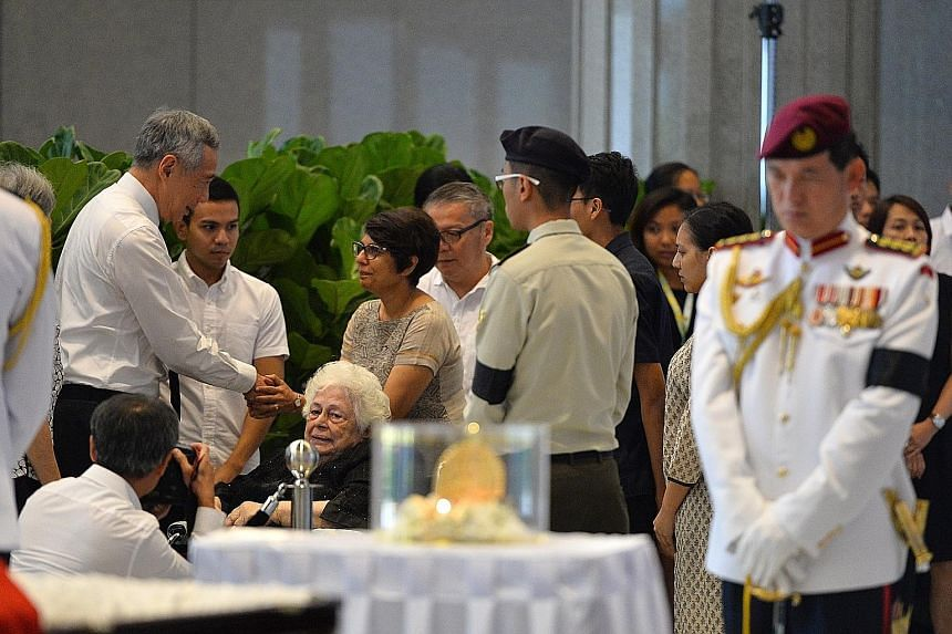 Above: PM Lee greeting Ms Juthika, daughter of Mr Nathan, at Parliament House yesterday. Also present was Mr Nathan's wife, Madam Urmila Nandey (in a wheelchair). Right: Former MP Mr Chiam being assisted by his wife, former Non-Constituency MP Mrs Ch