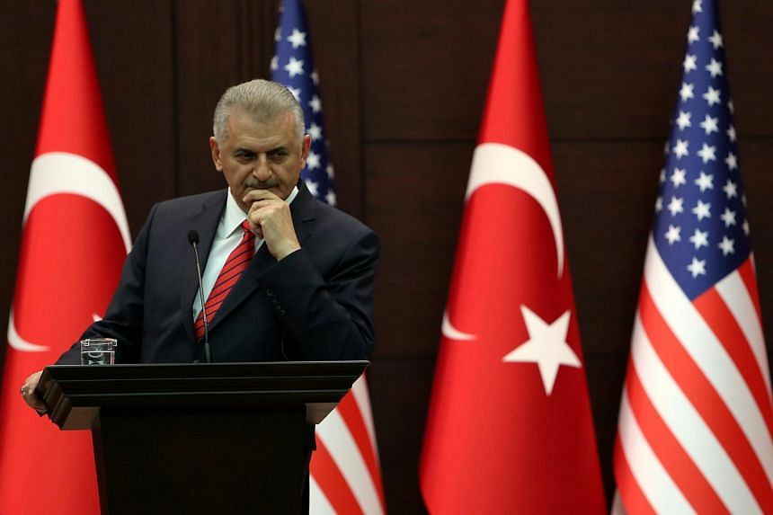 Turkish Prime Minister Binali Yildirim listens to remarks by US Vice President Joe Biden (unseen) during a joint news conference following their talks in Ankara, Turkey on Aug 24, 2016.