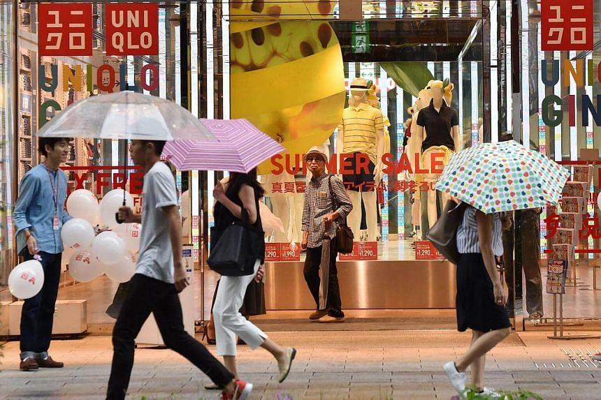 Pedestrians walk past Japanese retail store Uniqlo in Tokyo on July 15.