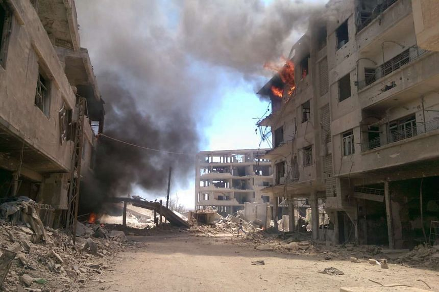 Fire and smoke gush out of buildings following reported air strikes on Daraya on Aug 16, 2016.