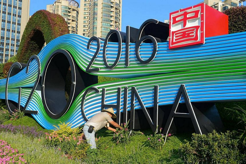 A gardener tends to the flowers in front of a Hangzhou G20 summit signboard.