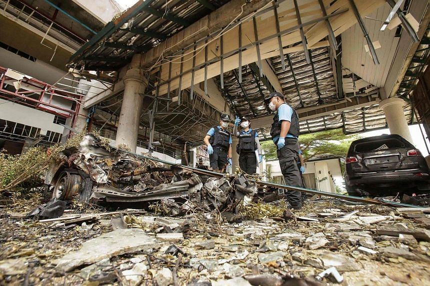 A forensics unit inspects the site of the deadly bomb blast outside of a hotel in the southern Thai province of Pattani on Aug 24.