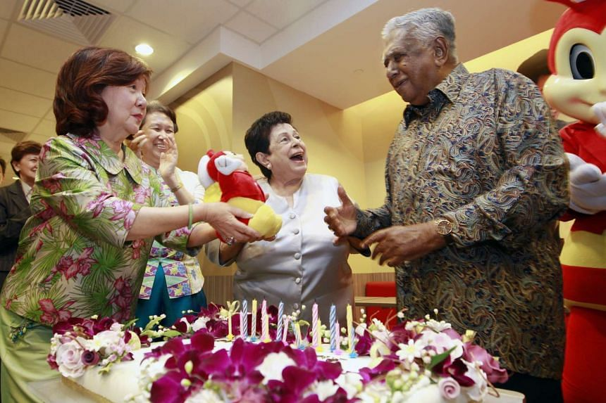 Mr S R Nathan sharing a moment with his wife Urmila Nandey (second from right) during his birthday celebration at the official opening of fast-food group Jollibee on July 3, 2013.
