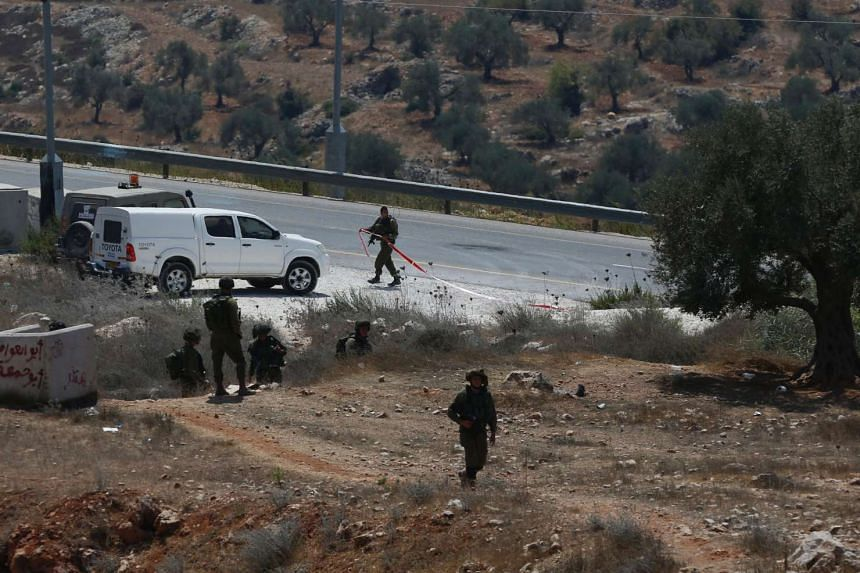 Israeli soldiers seal off the scene where a suspected Palestinian man was reportedly shot dead by Israeli troops at the entrance to the West Bank village of Silwad on Aug 26, 2016.