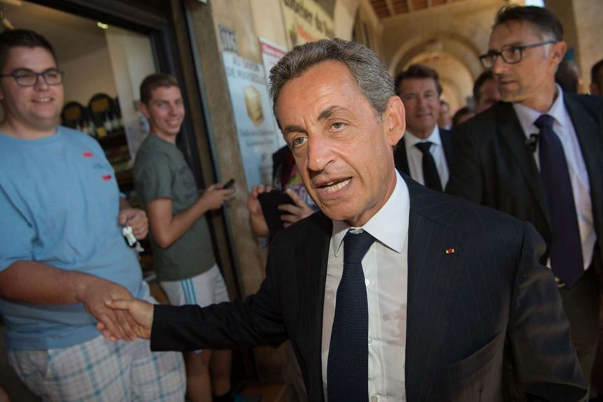 Former French president Nicolas Sarkozy (centre) shakes hands with people as he leaves the city hall following a meeting on Aug 25, 2016, in Marseille.