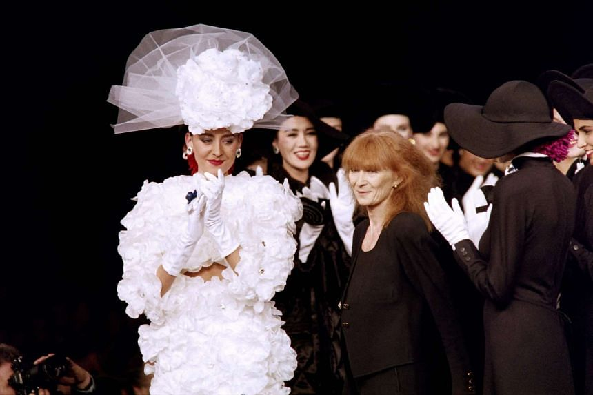 French fashion designer Sonia Rykiel is applauded by the crowd and her models after a show in Paris in 1987.