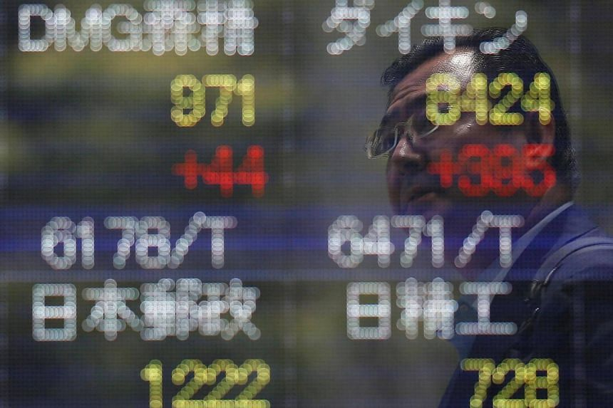 A man is reflected on a stock quotation board outside a brokerage in Tokyo.