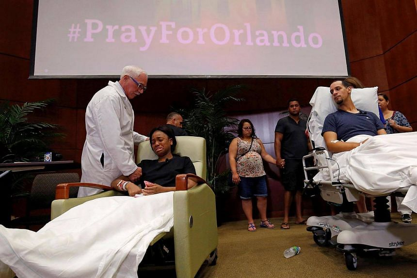 Gunshot survivor Patience Carter (second from left) is comforted by Dr Neil Finkler as fellow survivor Angel Santiago (right) looks on at a news conference at Florida Hospital Orlando, June 14.