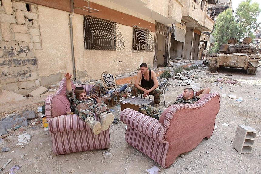 Syrian army soldiers rest in a street in the government-controlled part of the besieged town of Daraya on Aug 26, 2016, as thousands of rebel fighters and civilians prepared to evacuate under an accord struck a day earlier.