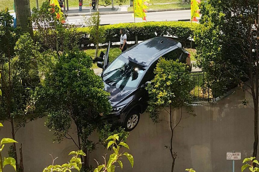 An SUV hung over a the basement of a building after it crashed into a railing on Bukit Batok Street 23.