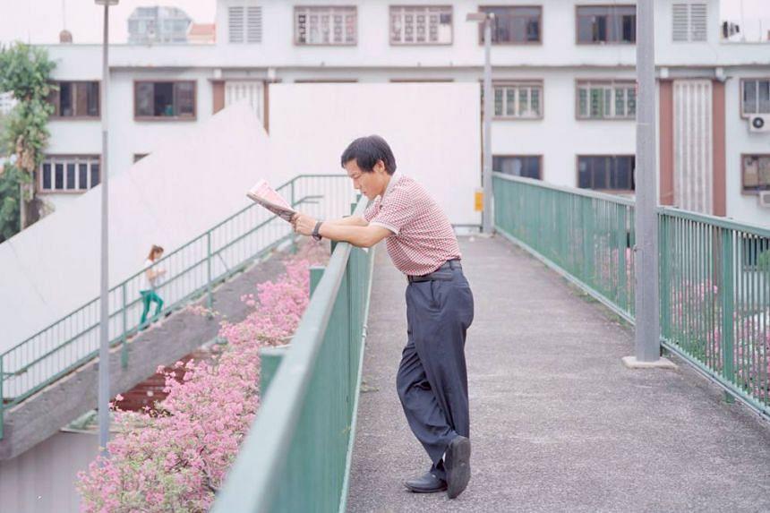A man reading a newspaper on an overhead bridge.