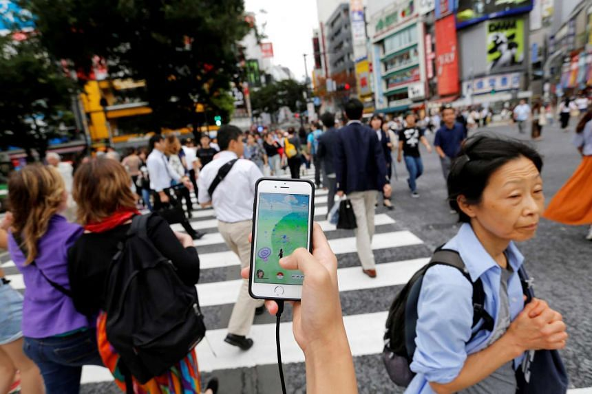 """A man plays """"Pokemon Go"""" on his mobile phone as he walks at a busy crossing in Shibuya district in Tokyo, Japan on July 22."""