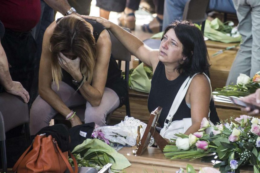 A relative of a victim cries in front of the coffin before the mass funeral for some of the victims of the earthquake.