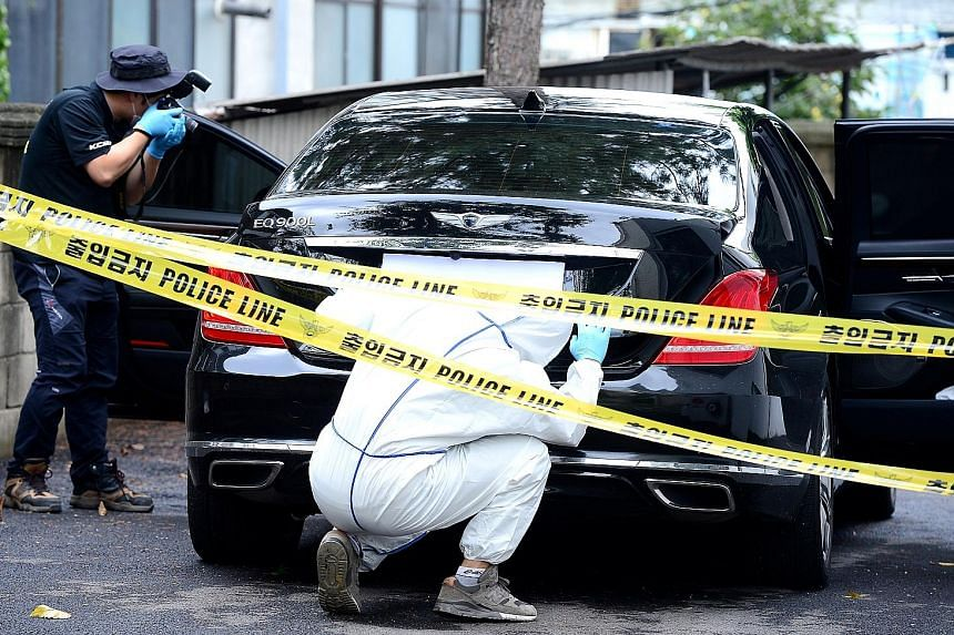 Investigators examining a car owned by Mr Lee at a police station in Yangpyeong, South Korea, yesterday. The body of the Lotte Group vice-chairman was reported to be found hanged from a tree near a hiking trail in the town. Mr Lee had been with Lotte