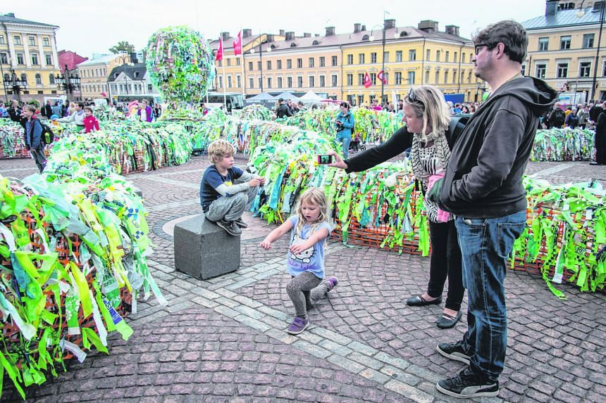 A family looking at the octopus-shaped installation Sea Lives by South Korean artist Choi Jeong Hwa on Thursday. The artwork, made of recycled plastic, was displayed during the Night Of The Arts in Senate Square in Helsinki, Finland. Recycled materia