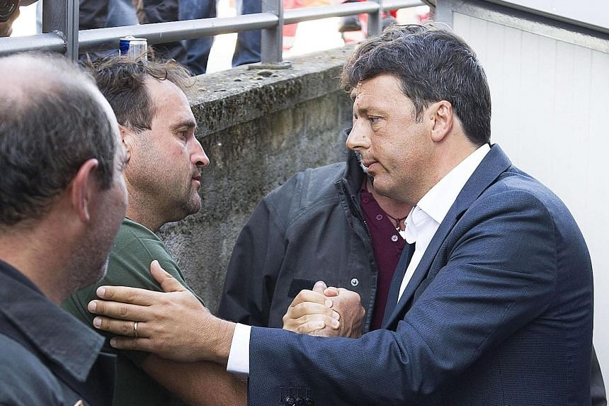 Mr Renzi with rescue workers in the town of Amatrice.
