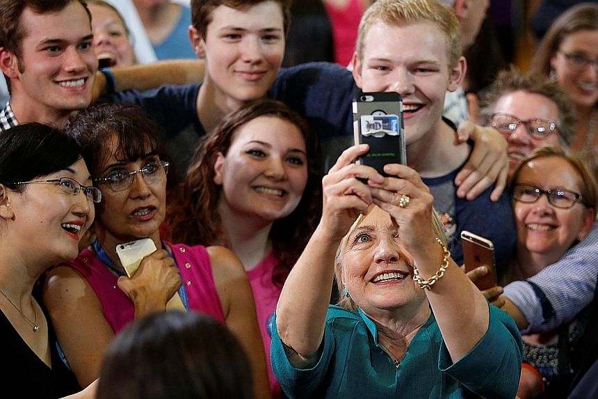 Mrs Clinton taking a wefie with supporters during a rally at Lincoln High School in Des Moines, Iowa, earlier this month. She is out to court minorities who are critical to her chances of winning in the Nov 8 election.