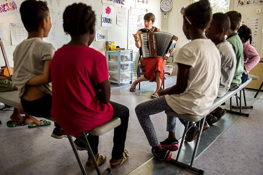 Migrant children having lessons yesterday in Calais in northern France. While big declines in refugee numbers followed the Turkey pact, EU governments had already closed transit routes north from Greece earlier by reintroducing internal border checks