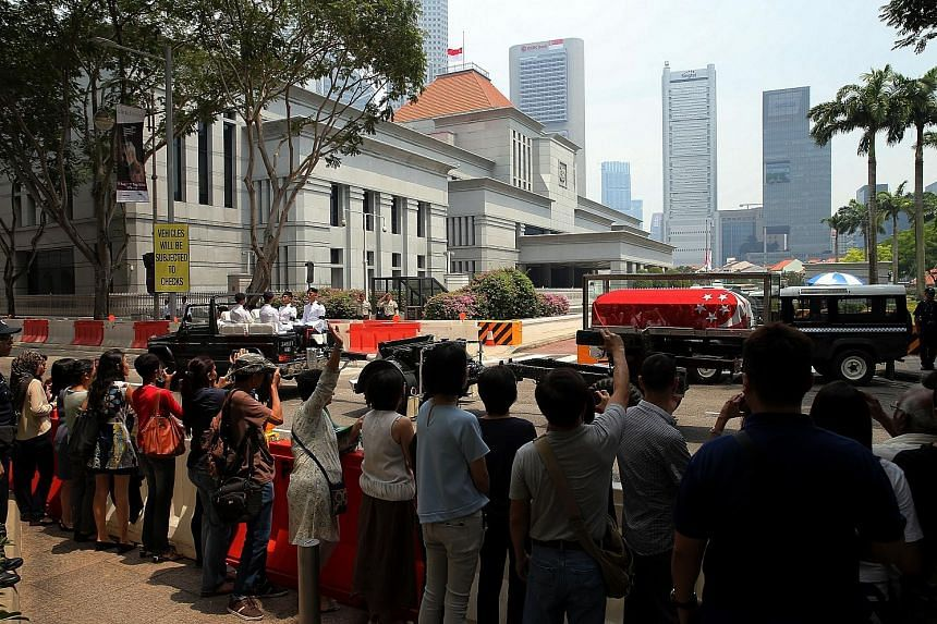 Above: PM Lee paying his respects to Mr Nathan at the state funeral service yesterday. Right: People lining the street across from Parliament House as Mr Nathan's cortege passed on its way to the University Cultural Centre at Kent Ridge.