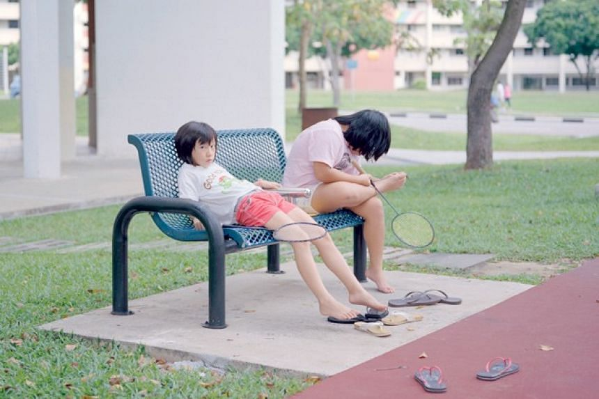 Two girls slumped on a bench after a game of badminton.