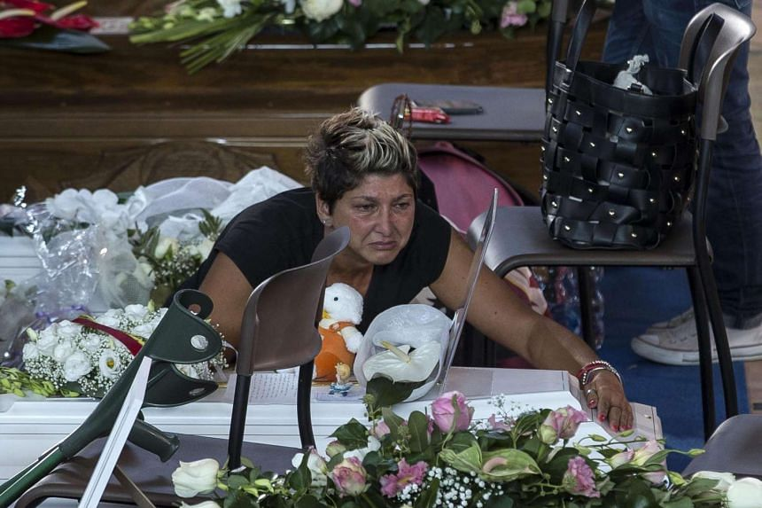A woman embraces the coffin of a victim before the mass funeral in Ascoli Piceno, Italy, Aug 27, 2016.